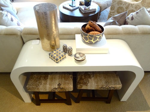 Love the mix of the modern console with the old rug ottomans beneath it.
